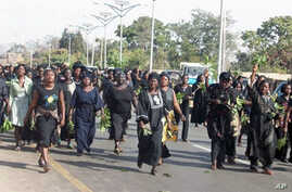 Hundreds of women march through the streets to protest the killing of women and children and destruction of properties in Jos, Plateau State in central Nigeria on January 31, 2011