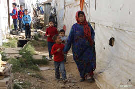 Syrian refugees walk in an informal settlement in Zahle in the Bekaa Valley, Lebanon, Oct. 16, 2014.