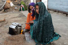 FILE - internally displaced girls warm up by a stove after their family left their village in the Achin district of Afghanistan, due to clashes between the Islamic State group and other insurgent groups, on the outskirts of Jalalabad, east of Kabul.