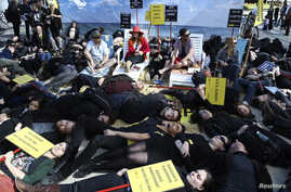 Human rights activists stage a protest on a sandy beach to call on EU leaders to do more to protect the rights and lives of migrants, refugees and asylum seekers arriving at Europe's borders, ahead of a European Union leaders summit in Brussels, Marc