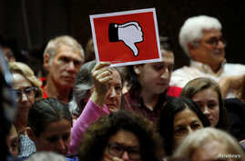 A voter holds up a sign during a town hall meeting with constituents by U.S. Representative Leonard Lance, R-N.J., in Cranford, New Jersey, May 30, 2017.