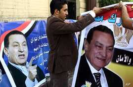Supporters of Egyptian President Hosni Mubarak hold up portraits of their 82-year-old leader during a small demonstration in his support held in Cairo on October 14, 2010 to mark the 29th anniversary of his accession to power in 1981, following the a