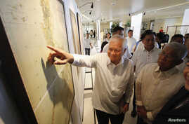 Philippines' Foreign Secretary Albert Del Rosario, points to a ancient map on display while Defense Secretary Voltaire Gazmin (R) looks on during the opening, at a Catholic university in Manila, Sept. 11, 2014.
