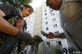 An armed pro-Russian separatist (L) and a man examine fragments of spent ammunition in central Donetsk, July 29, 2014.