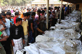 Bangladeshi people identify the bodies of their relatives died in a fire at a garment factory in the Savar neighborhood in Dhaka, Bangladesh, Nov. 25, 2012.