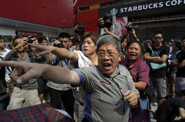 Local residents shout to a pro-democracy protester at a main street at Mong kok district in Hong Kong Friday, Oct. 17, 2014.