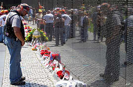 Visitor reading the names on the memorial wall