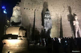 Tourists and Egyptians look at a huge granite statue of Ramses II,, center, after the completion of the restoration work, hours after the Egyptian Ministry of Antiquities revealed the contents of a Pharaonic cemetery on the western bank in Luxor, sou