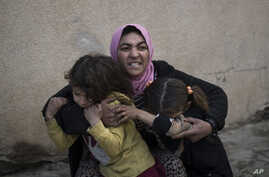 FILE - A woman holds her daughters as gunshots are heard in a neighborhood recently liberated by Iraqi security forces in western Mosul, Iraq, March 14, 2017. As the U.S.-led coalition ramps up the fight against the Islamic State group in Iraq and Sy