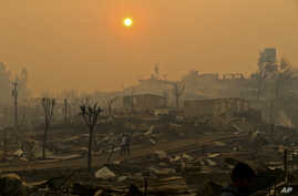 A couple walks through a neighborhood destroyed by wildfires in Chile's Santa Olga community, Jan. 26, 2017. Officials say the town was consumed by the country's worst wildfires.
