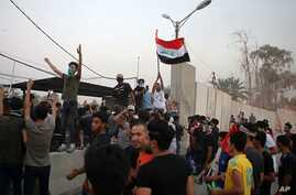 Protesters raise the Iraqi flag at the gate of the Iranian consulate building before storming and burning it in Basra, 340 miles (550 km) southeast of Baghdad, Iraq, Sept. 7, 2018.