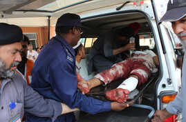 Pakistani volunteers carry an injured person who arrived from Mardan, at a local hospital in Peshawar, Pakistan, Sept. 2, 2016.