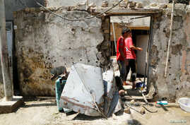 People inspect a damaged house after a suicide bomb attack in Baghdad's mainly Shi'ite district of Sadr City, Iraq, May 30, 2016.