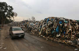 A car passes by a pile of garbage in Karantina, east Beirut, Lebanon, Dec. 17, 2015.