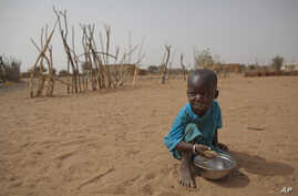 FILE - А boy is seen eating dry couscous in the village of