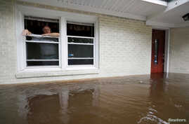Obrad Gavrilovic peers out the window of his flooded home while considering whether to leave with his wife and pets, as waters rise in Bolivia, N.C., Sept. 15, 2018.