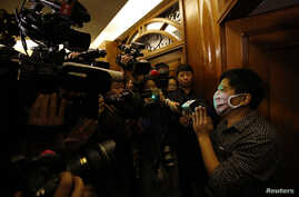 A family member of a passenger onboard the missing Malaysia Airlines Flight MH370 talks to reporters in a hotel in Beijing, March 14, 2014.