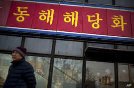 FILE - A man walks past a branch of the North Korean-operated Haedanghwa restaurant in Beijing.