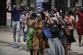 Residents are ordered out of a building with their hands in the air as security forces pursue protesters in Kampala, Uganda, Aug. 20, 2018.