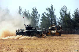 A Turkish army tank and an armored vehicle are stationed near the border with Syria, in Karkamis, Turkey, Aug. 23, 2016. Turkish media reports say Turkish artillery on Tuesday launched new strikes at Islamic State targets across the border in Syria.