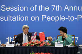U.S. Secretary of State John Kerry, left, holds the hand of Chinese Vice Premier Liu Yandong after delivering a speech for the plenary session of the 7th annual U.S.-China High-Level Consultation on People-to-People Exchange at the National Museum in