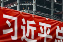 """In this April 16, 2017 photo, workers prepare to load cables at a building construction site as a propaganda banner reads """"The Party Secretary General Xi Jinping"""" on display at the Central Business District in Beijing."""