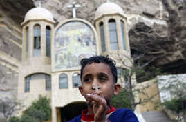 An Egyptian Christian boy holds a cross pendant outside a Coptic church in Cairo. Egyptian security forces began throwing up a cordon of steel as Coptic Christians prepared to mark Christmas after a New Year's Day church bombing killed 21 people in A