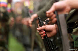 FILE - A fighter of the Revolutionary Armed Forces of Colombia (FARC) participates in a parade in the Villa Colombia camp near San Vicente del Caguan,Caqueta province, Colombia, April 29, 2000.