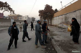A woman talks to Afghan policemen to allow her to pass through the road that leads to her home, as they stand guard near the site of a suicide attack that wounded Afghanistan's Intelligence Chief Asadullah Khalid in Kabul, December 6, 2012.