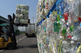 FILE - Packs of flattened polyethylene terephthalate (or PET) bottles are carried into a depot before being pulverized as part of a recycling process at Tokyo PET Bottle Recycle Co. in Tokyo, Aug. 13, 2002. Researchers in Britain and the United State