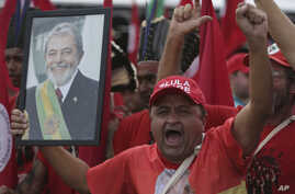 A supporter holds a photo of Brazil's jailed former president Luiz Inacio Lula da Silva, as he takes part in the Free Lula March, in Brasilia, Aug. 15 2018.