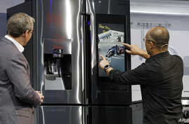 Yoon Lee, right, senior vice president, Samsung Electronics America, uses the Family Board on a refrigerator during a Samsung news conference at CES International in Las Vegas, Jan. 7, 2019.