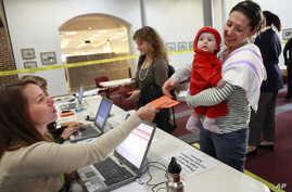 FILE - Election officer Devon Tutak, left, hands a verified voters registration form to Carly von Schaumburg, holding her daughter Alix von Schaumburg, at the polling site at Alexandria City Hall in Alexandria, Va.