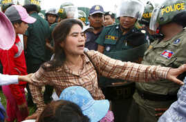 FILE - Tep Vanny of Boeung Kak lake is blocked by riot police officers during a protest rally near the prime minister's residence in Phnom Penh, Cambodia, July 2, 2013.