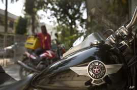 A delivery boy sits on his Indian motorcycle and looks at a Harley Davidson Fat Boy motorcycle parked in a residential area in New Delhi, India, March 1, 2017.
