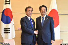 South Korea's President Moon Jae-in, left, shakes hands with Japan's Prime Minister Shinzo Abe before their meeting at Abe's official residence in Tokyo, May 9, 2018.