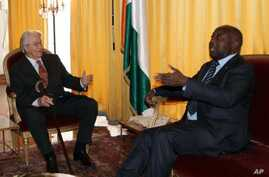 Former French foreign minister Roland Dumas (L) talks with Ivory Coast leader Laurent Gbagbo at the presidential palace in Abidjan, Dec 30 2010.