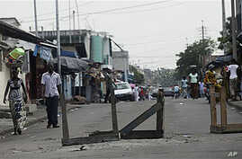 People walk down a road barricaded with tables, in Abidjan, Ivory Coast, 17 Dec 2010