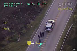 In this image made from a Friday, Sept. 16, 2016 police video, Terence Crutcher, top, is pursued by police officers as he walk to an SUV in Tulsa, Okla.