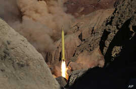 In this photo obtained from the Iranian Fars News Agency, a Qadr H long-range ballistic surface-to-surface missile is fired by Iran's Revolutionary Guard, during a maneuver, in an undisclosed location in Iran, Wednesday, March 9, 2016.