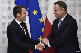 FILE - FILE - French President Emmanuel Macron (L) and  Polish President Andrzej Duda shake hands during their bilateral meeting on the sidelines of the NATO (North Atlantic Treaty Organization)  summit in Brussels, on May 25, 2017.