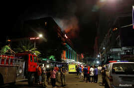 Evacuated employees and guests of hotels stand along a road and watch as smoke billows from a Resorts World building in Pasay City, Metro Manila, Philippines June 2, 2017.