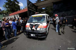 An ambulance carrying the bodies of those killed in the fire exits the Virgen de Asuncion home, in San Jose Pinula, on the outskirts of Guatemala City, Guatemala, March 8, 2017.