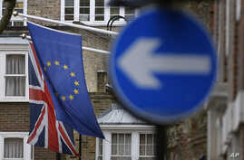 FILE - An EU flag hangs beside the Union flag at Europa House in London, Feb. 17, 2016. EU officials warn that a Brexit would force London to renegotiate free trade deals with EU member states.