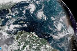 This enhanced satellite image made available by NOAA shows Tropical Storm Florence, center, in the Atlantic Ocean on Saturday, Sept. 8, 2018.