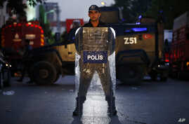 A Turkish police officer stands behind his shield as he secures the scene of a blast in Istanbul, Oct. 6, 2016.