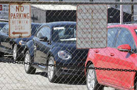 Volkswagen diesels are shown behind a security fence on a storage lot near a VW dealership Sept. 23, 2015, in Salt Lake City.