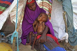 In this March 28, 2017 photo, newly displaced Somali mother Sahra Muse, 32, comforts her malnourished child Ibrahim Ali, 7, in their makeshift shelter at a camp in the Garasbaley area on the outskirts of Mogadishu, Somalia.