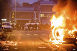 French police officers face protestors as a car burns in Bobigny, outside Paris, Feb. 11, 2017. A peaceful demonstration protesting the alleged rape of a black youth by police has degenerated, with small groups setting at least one vehicle afire and