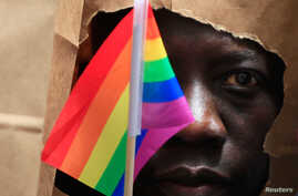 FILE - An asylum seeker from Uganda covers his face with a paper bag to protect his identity as he marches at a Gay Pride Parade in Boston, Massachusetts June 8, 2013.